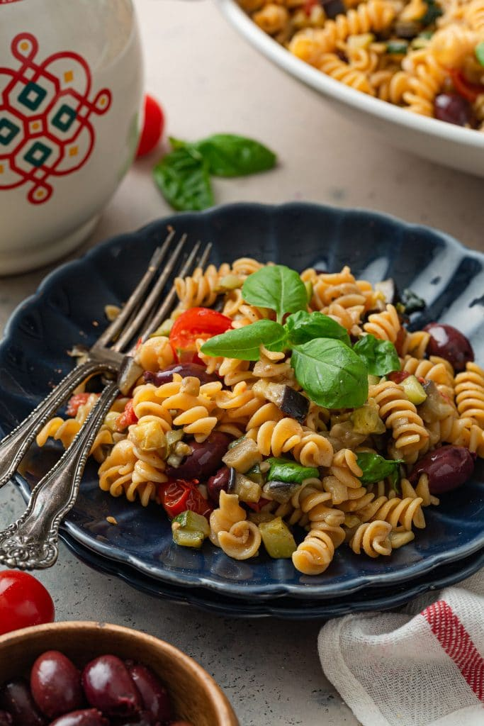 A plate of Mediterranean pasta, garnished with basil.