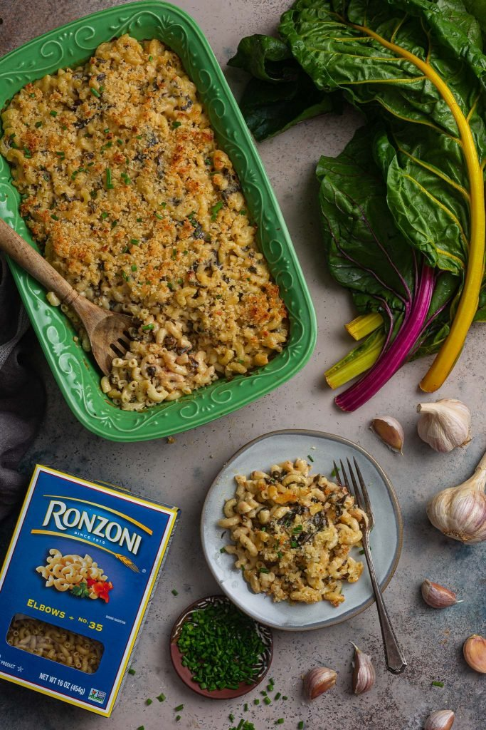 A serving scene. You can see the baking dish with roasted garlic mac and cheese, a plate with an individual portion, a Ronzoni box, a little plate with chives (for garnishing), some garlic and a bunch of Rainbow Chard.