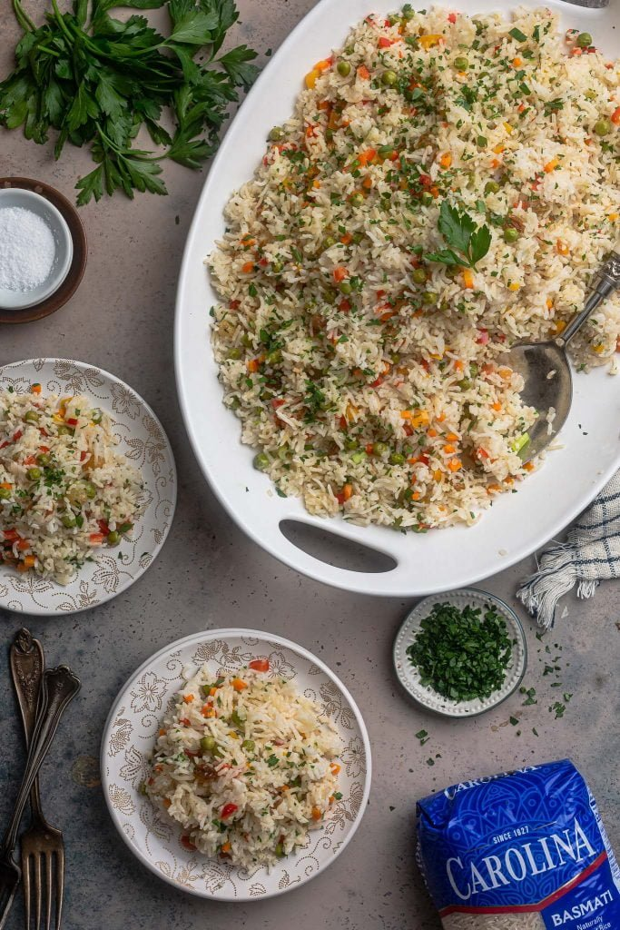 A serving scene. A big platter of arroz a grega and 2 individual servings on small plates.