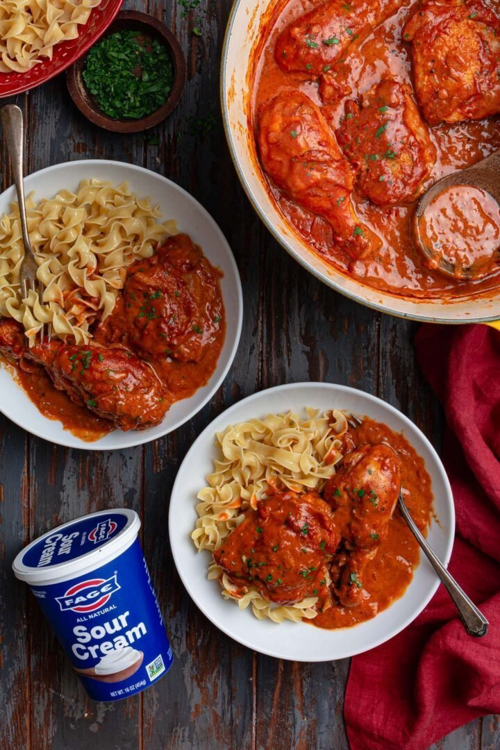 Two bowls with Paprika Chicken and a container of sour cream.