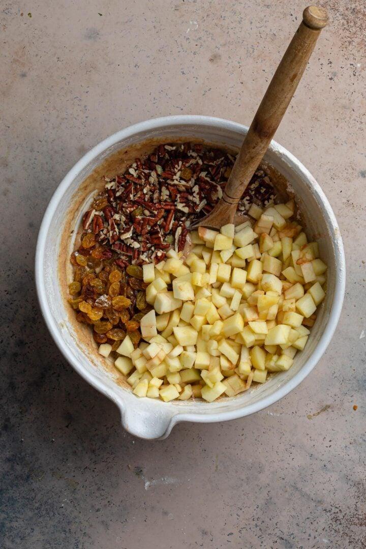 Adding the apple cubes, pecans and raisins.
