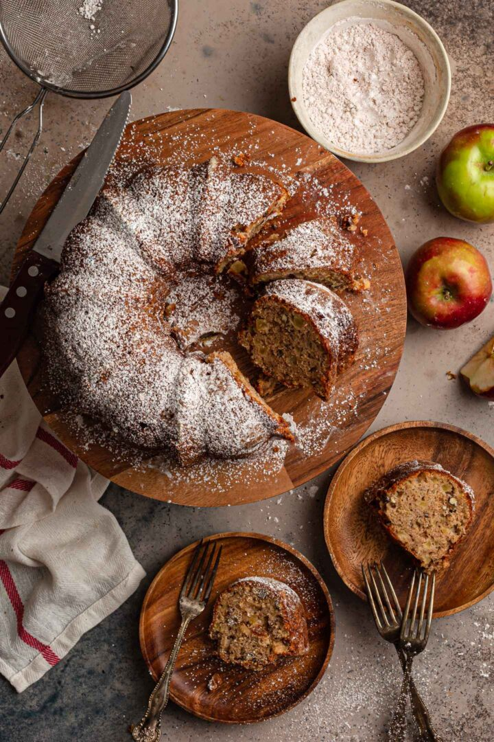 A serving scene. The apple bundt cake is sliced. Two slices in individual plates are shown.