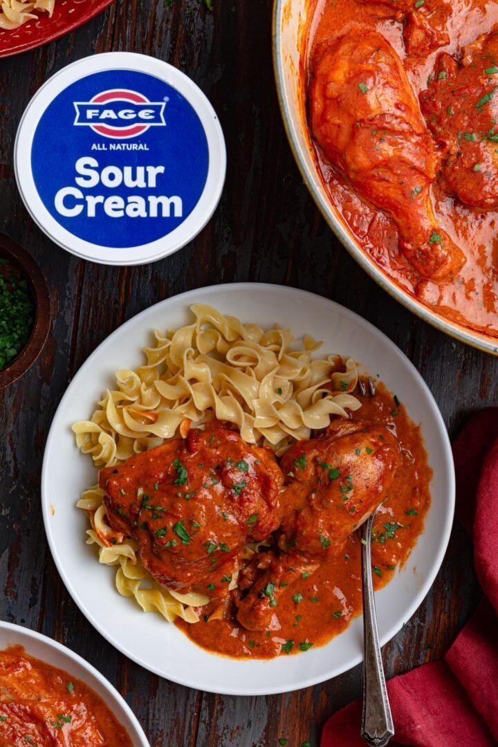 An overhead photo of a bowl of Chicken Paprikash with egg noodles.