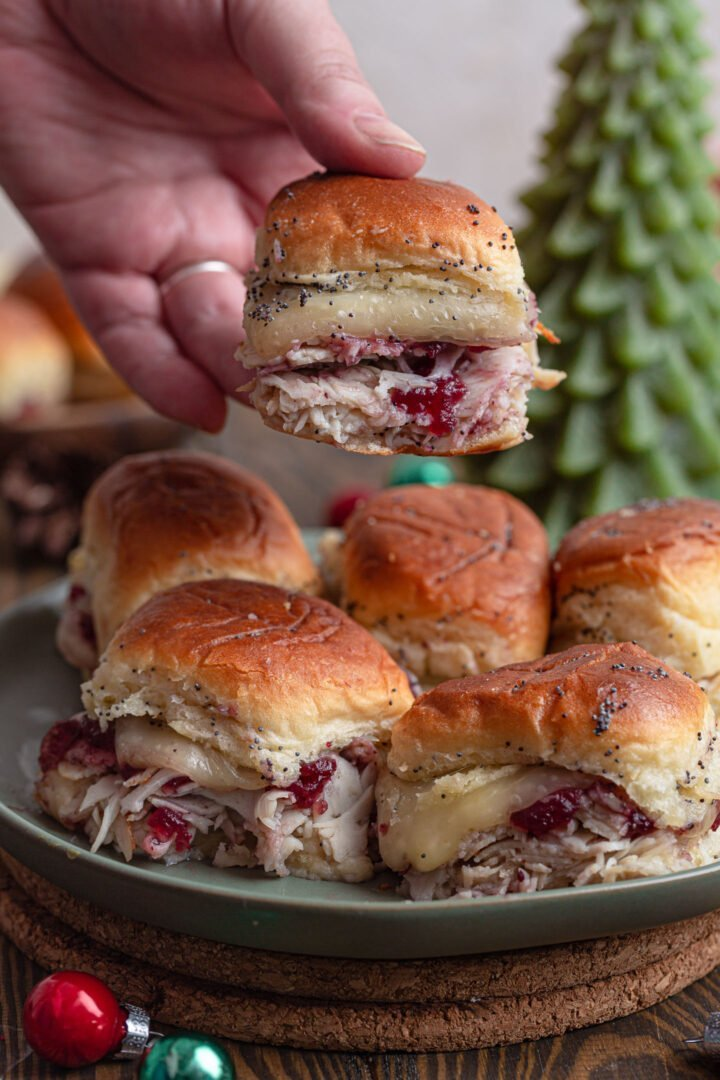 A hand lifting a turkey slider from a plate full of sliders.