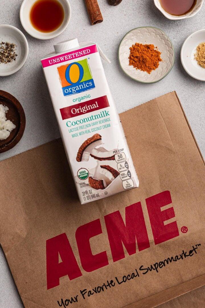 An ACME bag with a carton of O Organics coconut milk.