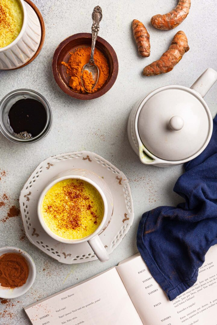 A mug of golden milk, a book, a towel, a bowl of cinnamon, a bowl of ground turmeric, a small glass with Maple syrup and some fresh turmeric.