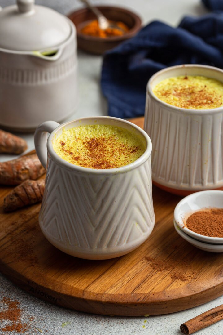 Two mugs of golden milk, garnished with cinnamon, on a board.
