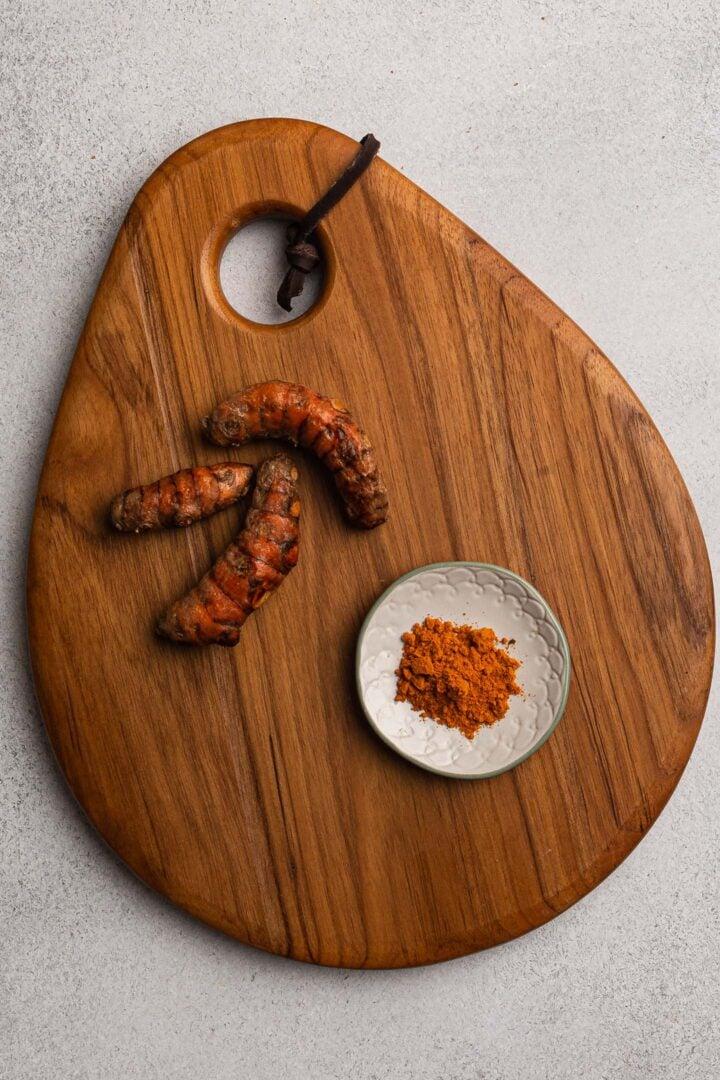 Fresh turmeric and ground turmeric on a board.