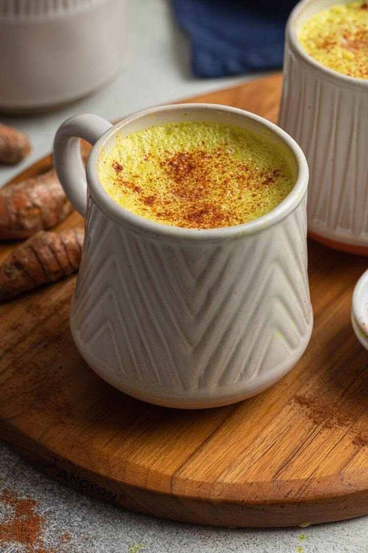 A mug of golden milk, garnished with cinnamon.