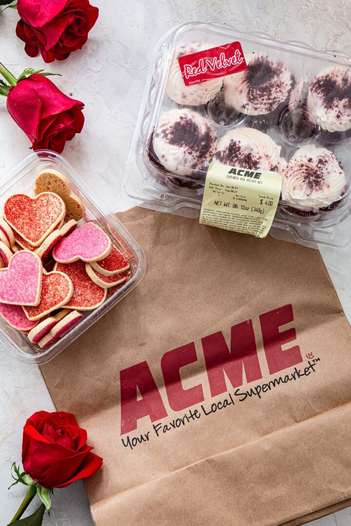 An ACME bag, a container of Red Velvet cupcakes, a container of heart shaped cookies and some roses.