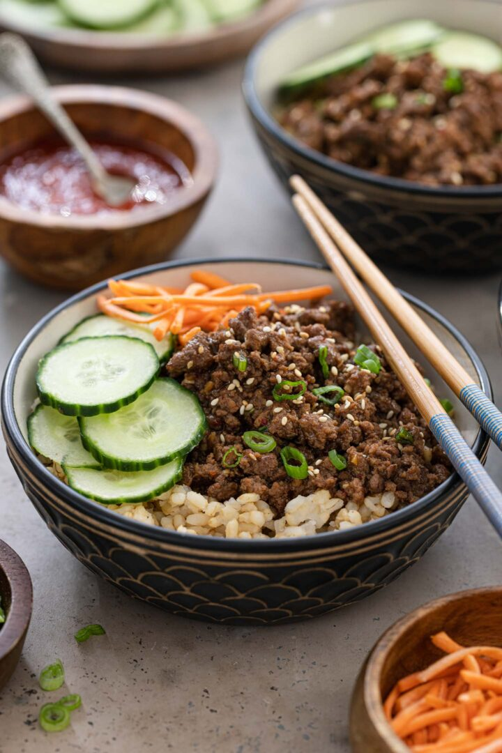 A Korean beef bowl topped with cucumber and carrots. Gochujang sauce on the sidel