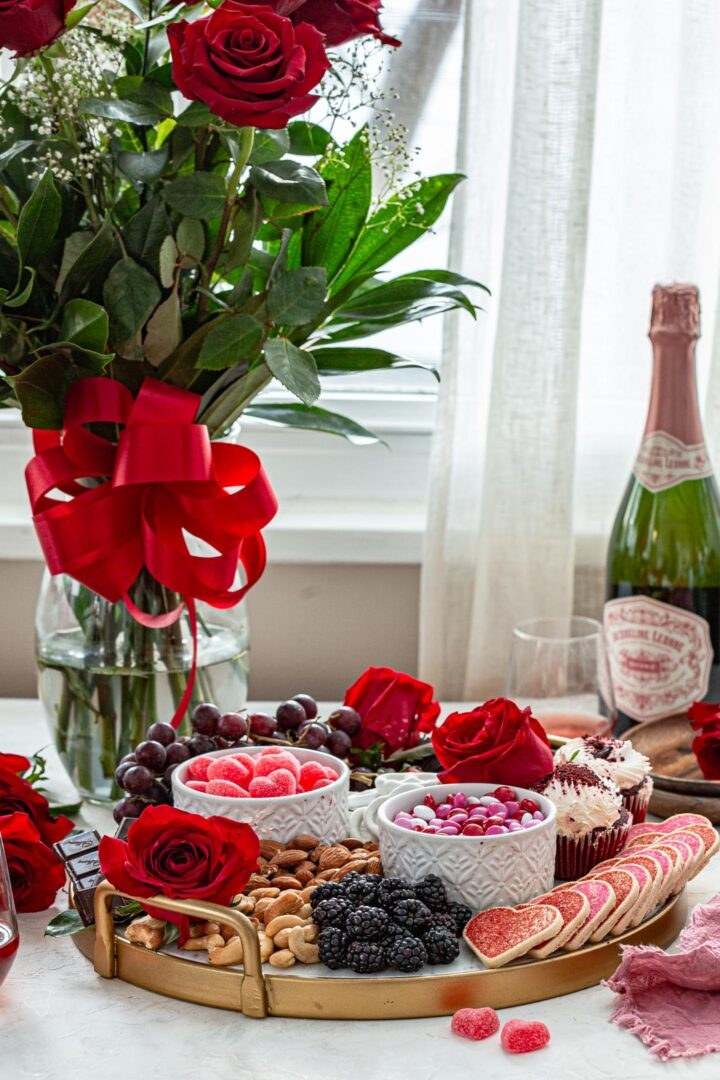 A Valentine's Day dessert charcuterie board, a vase of red roses and a bottle of champagne.