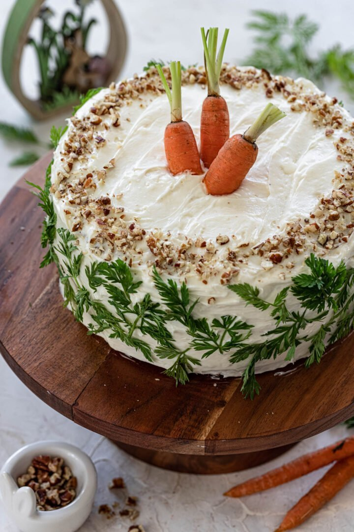 A beautiful classic carrot cake, decorated with chopped pecans, fresh carrots and carrot greens.