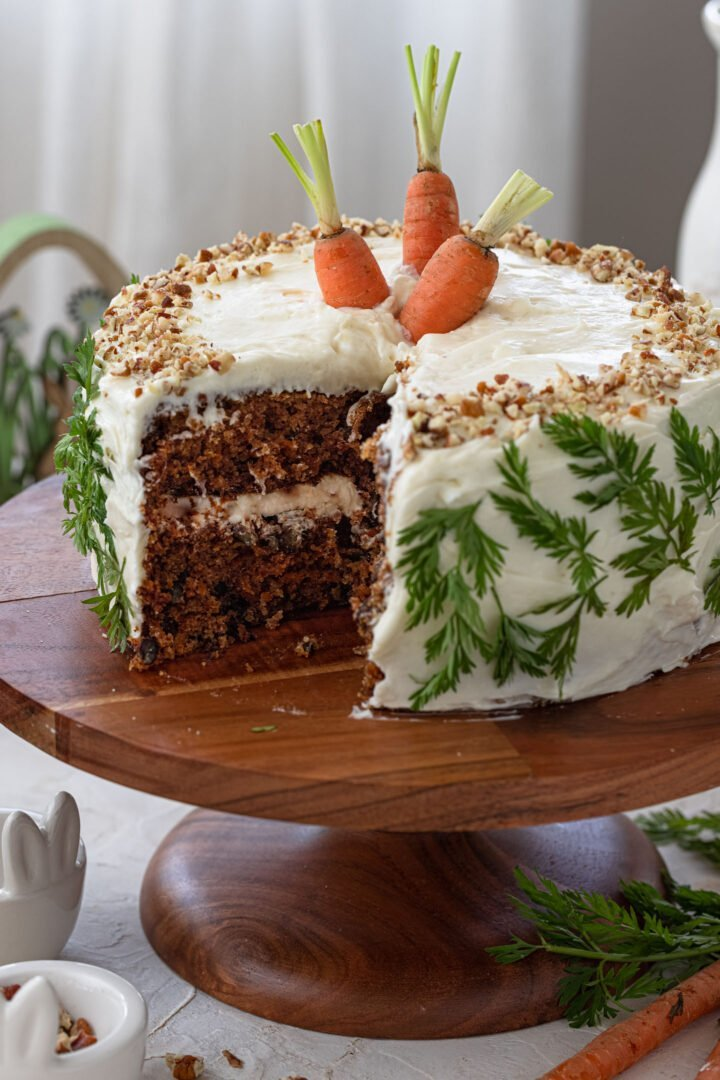 A cut carrot cake on a cake stand.