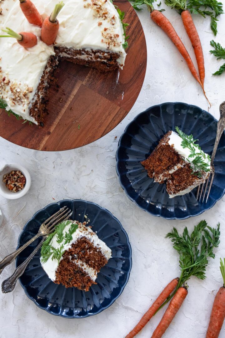 An overhead shot of a cut carrot cake and two individual carrot cake slices.