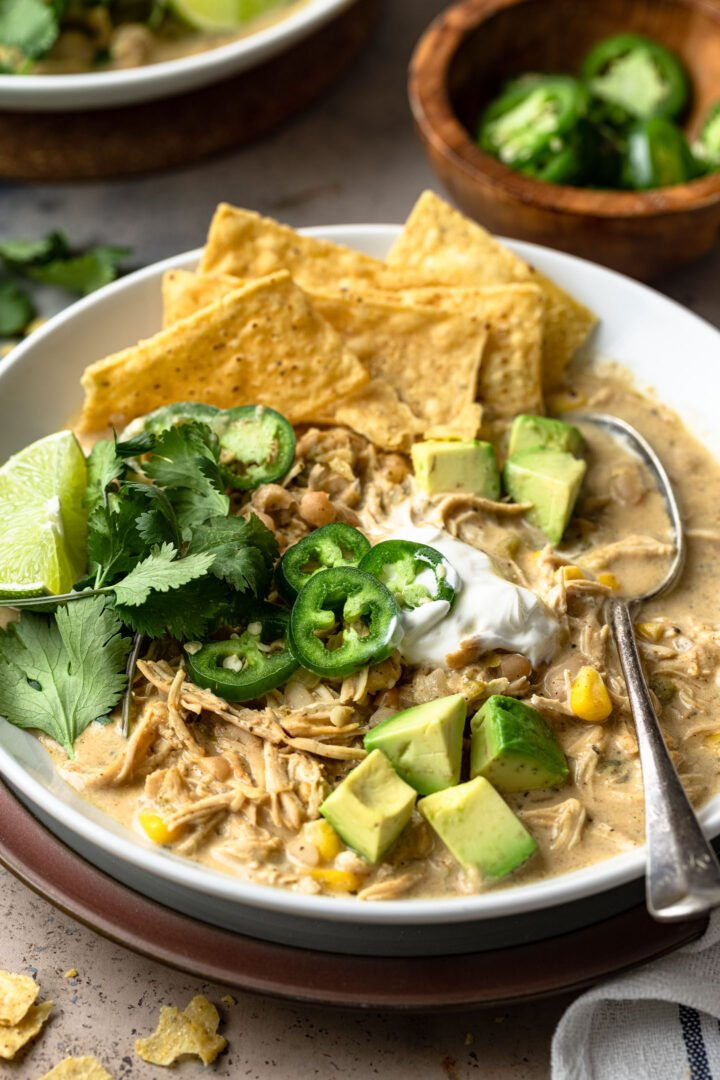 A close up photo of the white chicken chili with toppings.