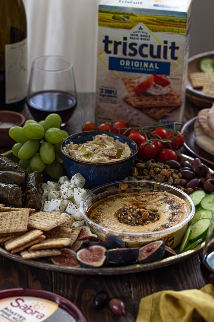 A mezze platter on a table with a box of TRISCUIT crackers.