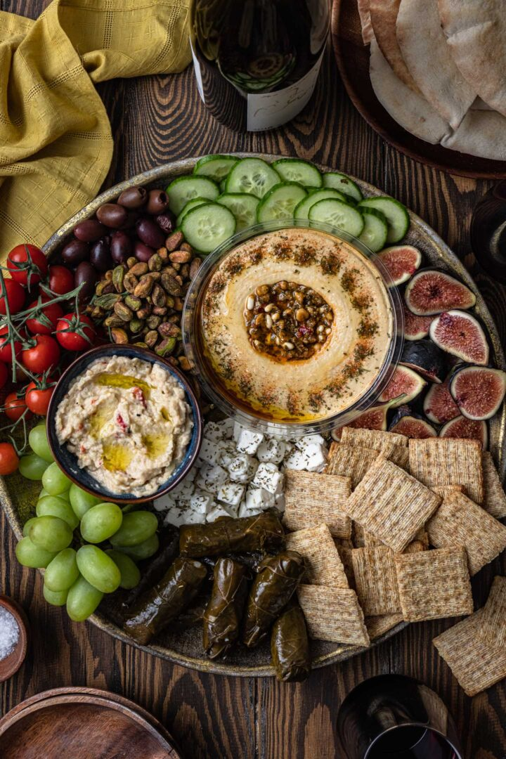 A beautiful mezze platter loaded with veggies, fruits, crackers, stuffed graped leaves, dips and nuts.