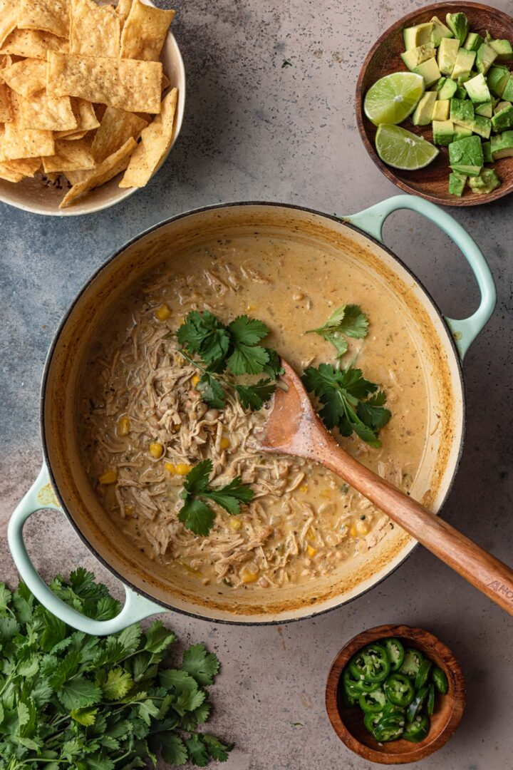 A photo of a Dutch Oven with white chicken chili. Toppings are on the side: jalapeños, cilantro, avocado and lime wedges, tortilla strips.