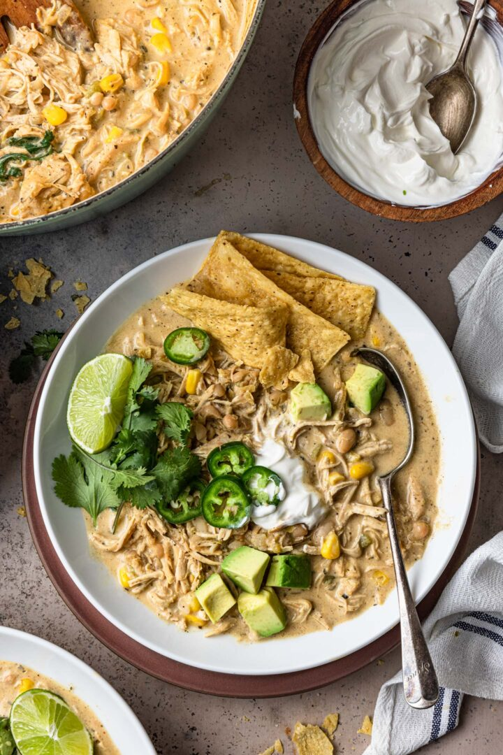 A bowl of white chicken chili, topped with tortilla strips, cilantro, jalapeños, avocados and a lime wedge.