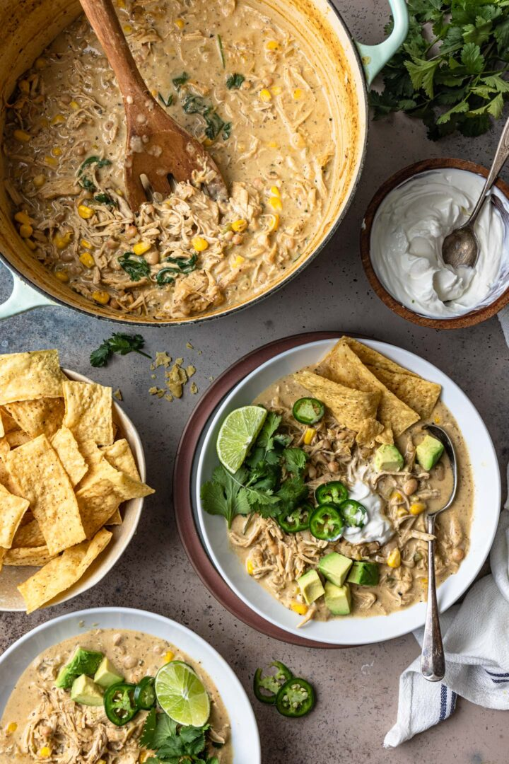 An overhead photo of a pot the white bean chicken chili, sour cream in a smaller bowl, tortilla strips and two individual bowls with the chili.