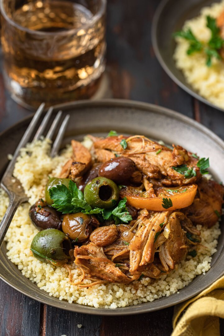 A close up shot of an individual serving of chicken tagine served over couscous.