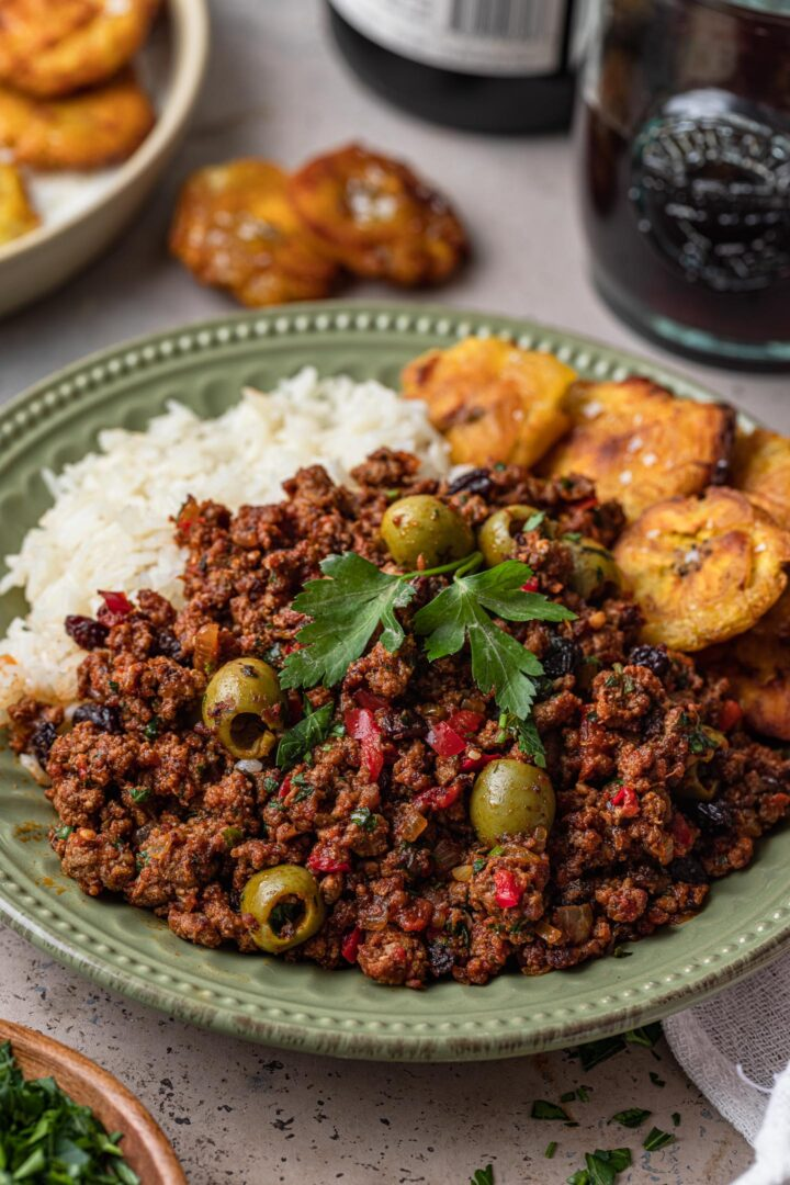 A plate of beef picadillo with rice and tostones.