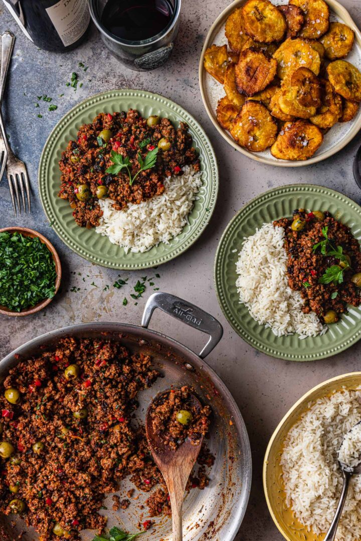 Serving scene. A pan of picadillo, along with two plates of picadillo served with rice. A bowl of white rice and a plate of tostones are also in the shot.