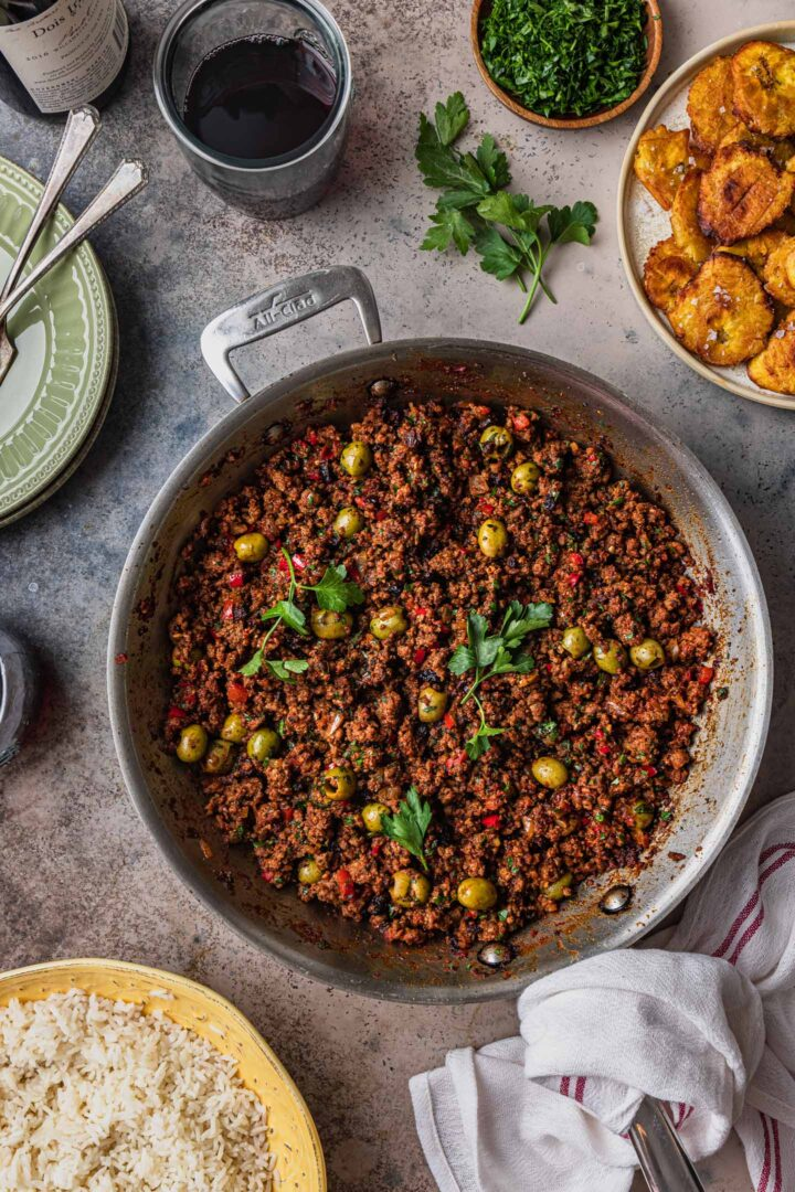 An overhead photo of a skillet of picadillo with rice and tostones served on the side along with red wine, parsley, plates, and a kitchen cloth.