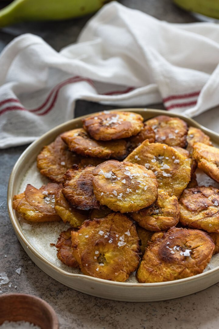 A platter of tostones sprinkled with flaky salt.