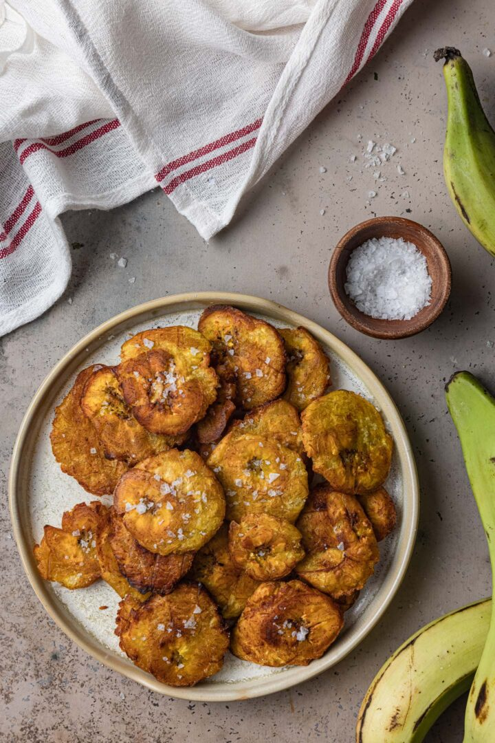 An overhead photo of a plate of tostones. A small bowl of salt, some green plantains and a kitchen towel are also in the shot.