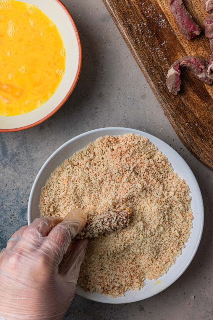 Coating the steak with the breadcrumbs.
