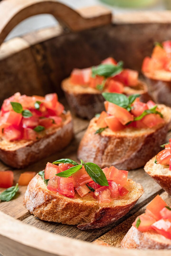 Close up of a wooden tray of tomato bruschetta garnished with basil.
