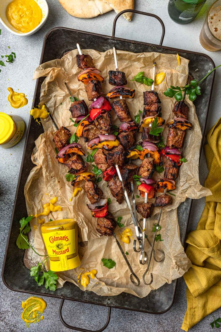 A tray of marinated steak kabobs and a bottle of mustard.