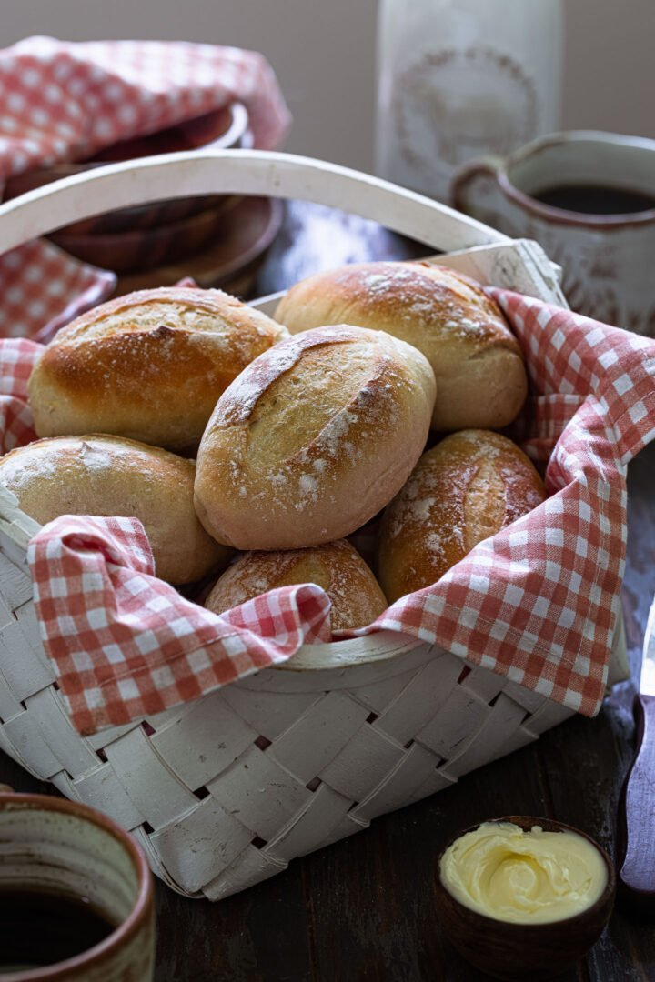 A basket of pão francês served with butter and coffee.