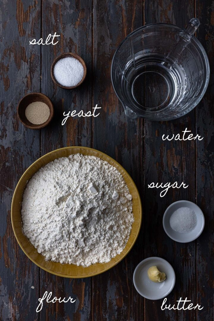 A photo of all the ingredients to make Brazilian bread rolls. Flour, yeast, water, sugar, salt and butter.