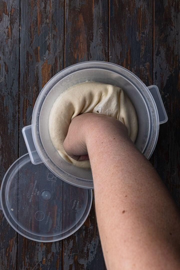 Punching down the dough to deflate it.