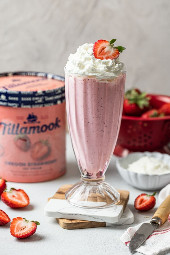 A glass of strawberry milkshake, topped with whipped cream and a strawberry.