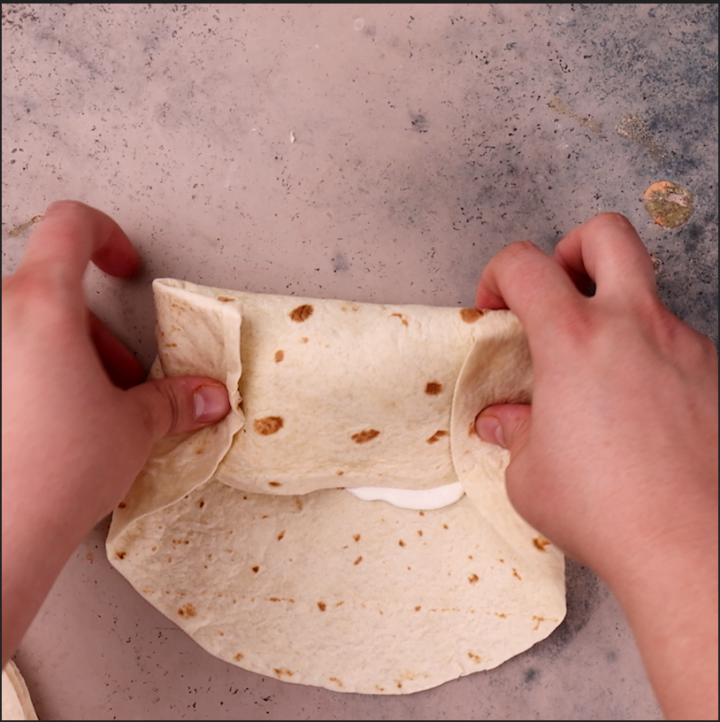 Rolling a beef burrito.