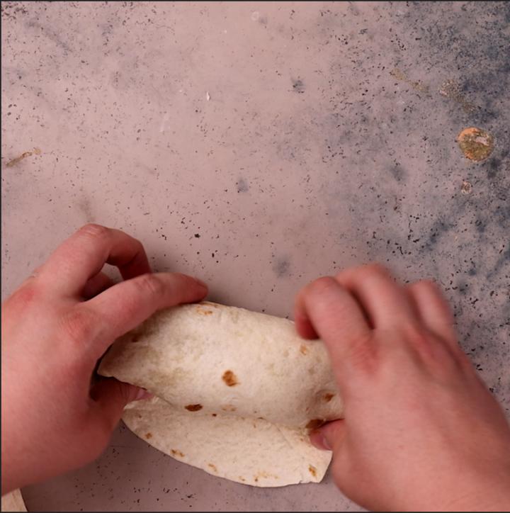 Rolling beef burritos.