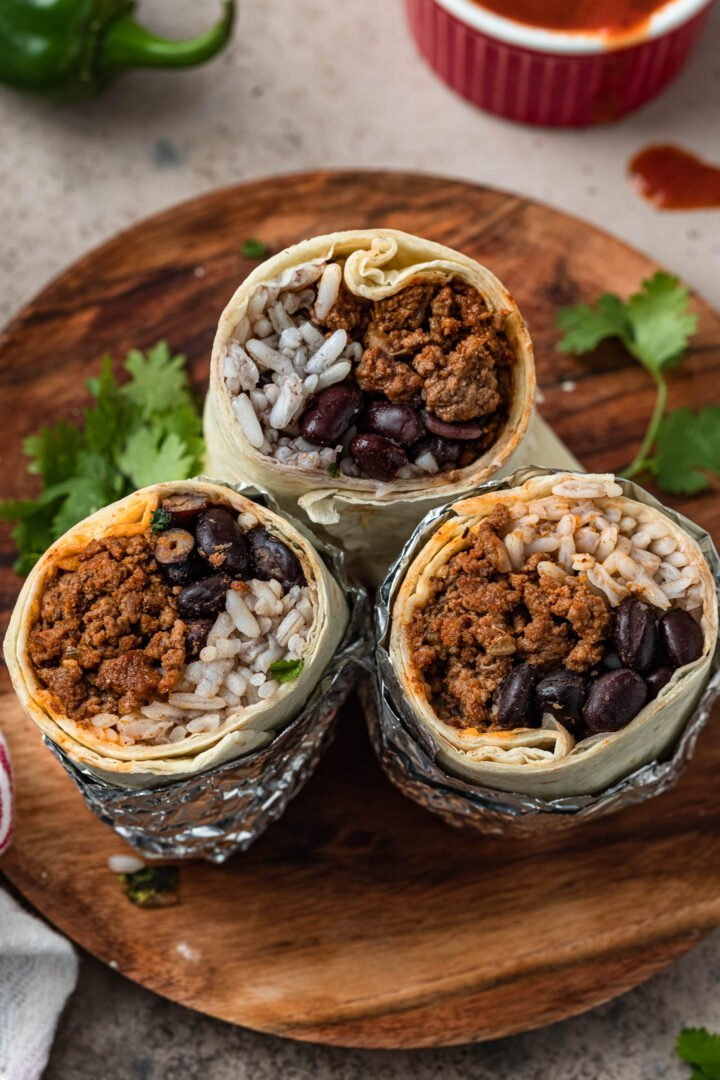 3 ground beef burritos halves on a plate. You can see the ground beef, rice and beans inside the burritos.