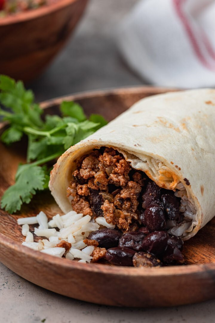 Rice, beans and ground beef spilling from a cut burrito.