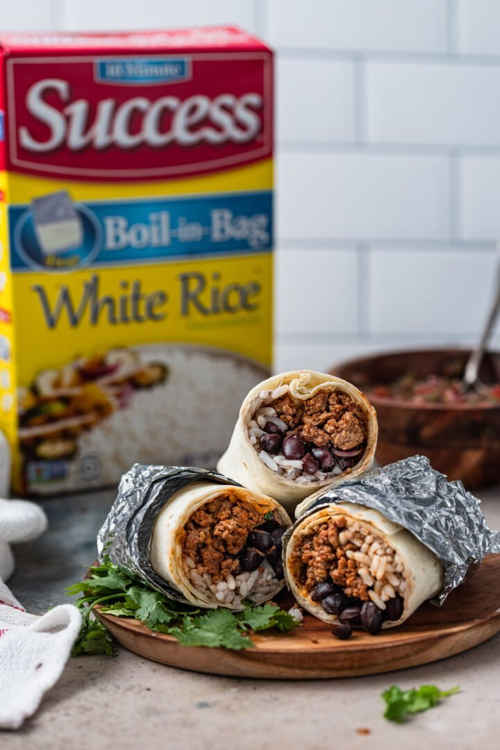 Ground beef burritos wrapped in foil with a Success rice box in the background.