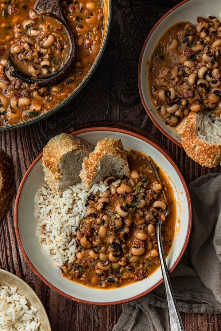 A serving of black-eyed peas with white rice and bread in a bowl.