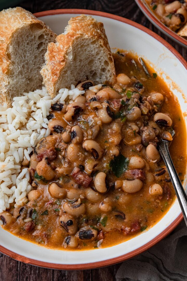 A close up of a serving of black-eyed peas in a bowl, with white rice and bread.