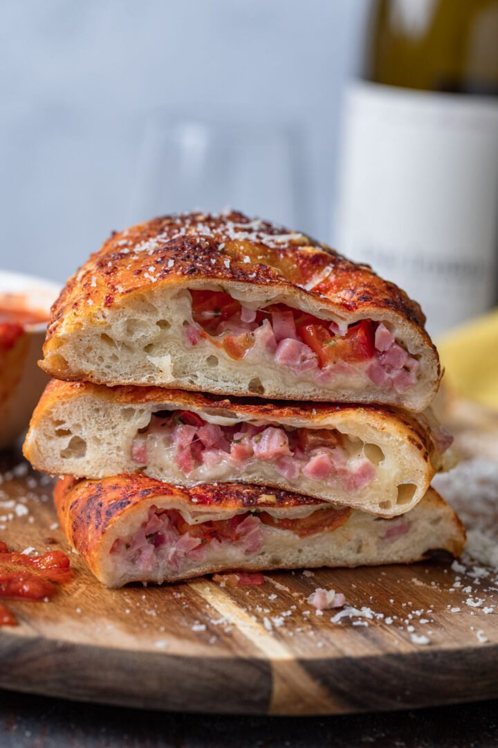 Three calzone halves. You can see the melty cheese, ham and tomatoes inside.