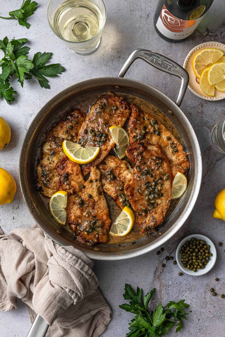 A pan with chicken piccata. On the side you can see some parsley, a few glasses of white wine, capers and lemons.