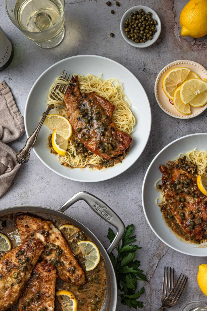 A pan with chicken piccata and two individual servings served over angel hair pasta.