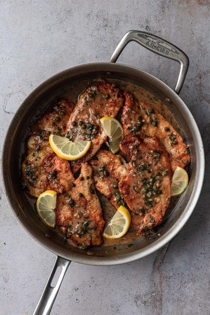 Chicken back in the pan with the piccata sauce.