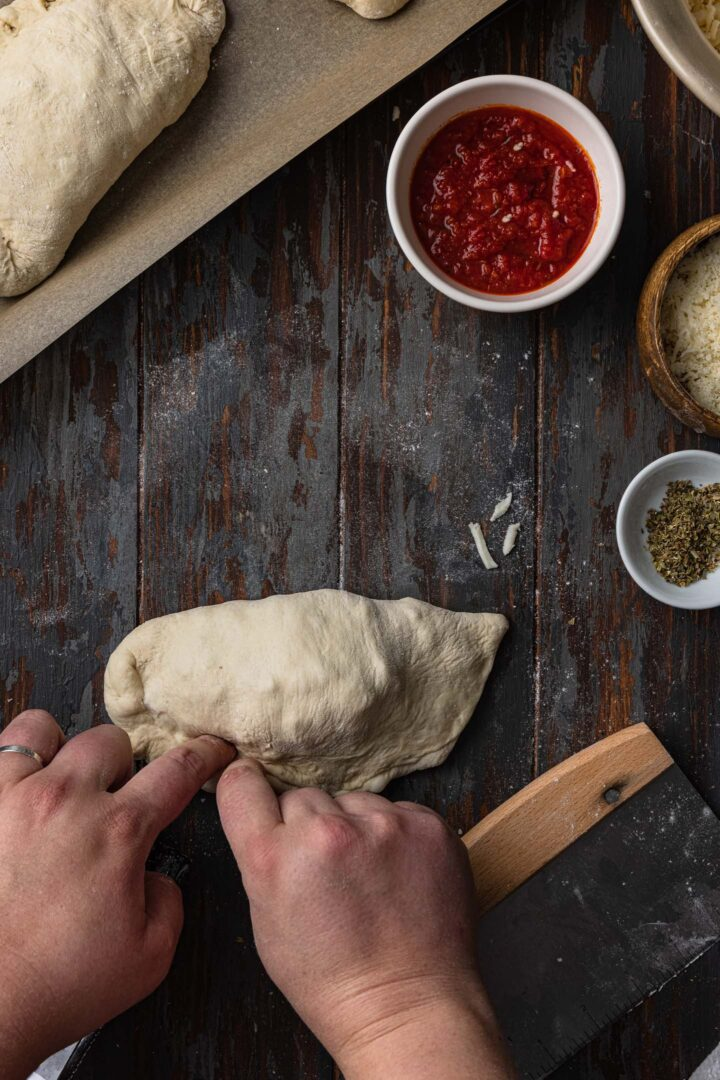 Crimping the edges of the calzone.